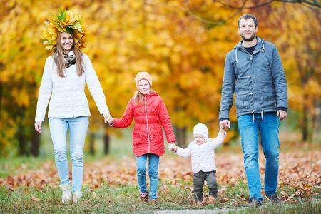 Photo pour Portrait of happy young family with baby girl in autumn park - image libre de droit