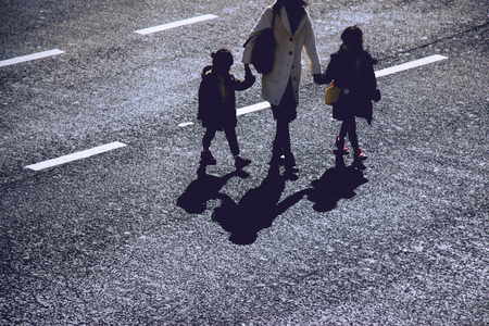 Silhouette of mother hold 2 girls hands across the street at Shibuya junction, Tokyo, Japan. the most famous junction and big crown people' landmark in Tokyo.