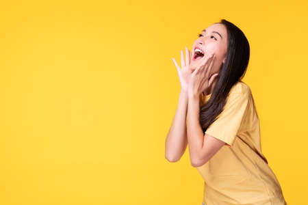 Photo pour Young woman covers her mouth surprised excited while looking at product on sale promotion or empty copy space over isolated yellow background. - image libre de droit