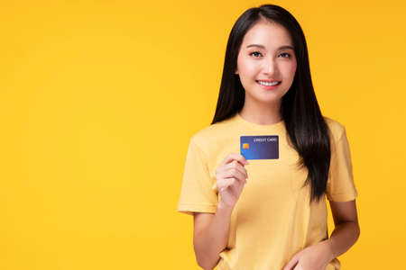 Photo pour Payment purchase and financial concept. Cheerful young woman wearing casual clothes while holding hand and credit card mockup while looking at empty copy space over isolated white background. - image libre de droit