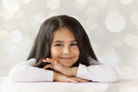 Photo pour Portrait of happy smiling child girl on a white lighting background - image libre de droit