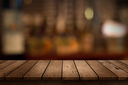 Photo pour wooden table with a view of blurred beverages bar backdrop - image libre de droit