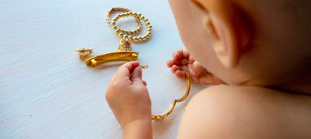Photo pour hands of child play with gold jewelry and bijouterie, on white background. concept of womens happines High quality photo - image libre de droit
