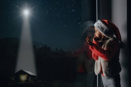 Photo for the child looks out the window on christmas of Jesus Christ. - Royalty Free Image