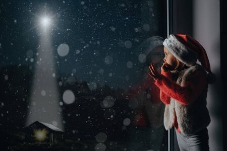 Photo for the child looks out the window on christmas - Royalty Free Image
