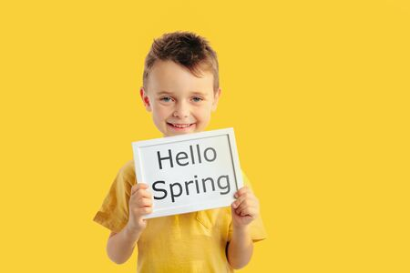 Photo pour Happy child boy holding a poster for your information on the blue background. Hello spring - image libre de droit
