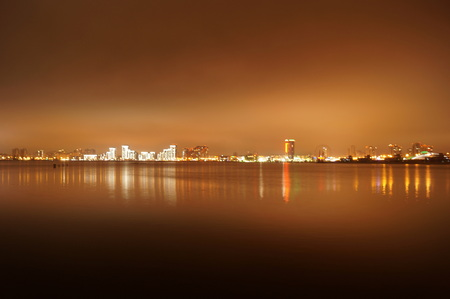 Brightly lit at night the city of Kazan, reflected in the waters of the river Kazanka, Russia.