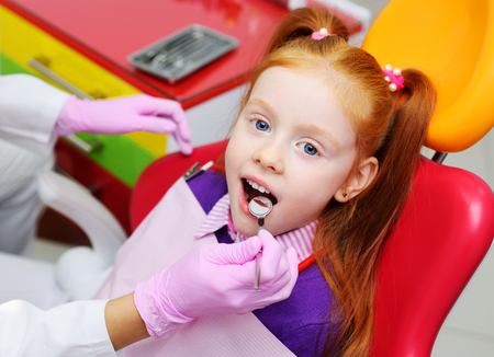Photo pour little girl smiling in red dental chair. The dentist examines the teeth of the childs patient. Pediatric dentistry - image libre de droit