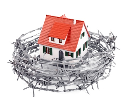 Protection of a miniature house with a barbed wire, concept