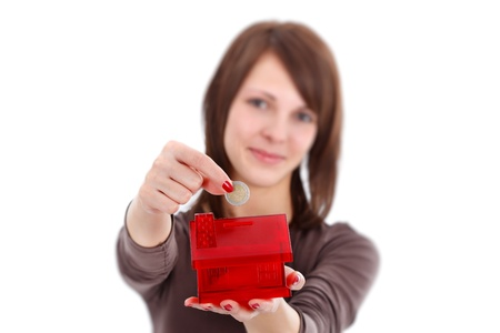 Woman putting coins in money box with form of a house