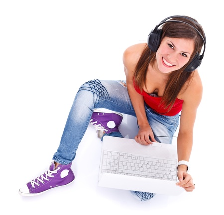 Portrait of a cute young smiling woman with headphones and notebook photographed from above. Studio shot.