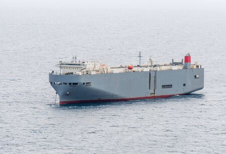 Foto de Large gray roll-on/roll-off (RORO or ro-ro) ships or oceangoing vehicle carrier ship anchor in the open sea. Roro ship designed to carry wheeled cargo such as cars, trucks, trailers, etc. - Imagen libre de derechos