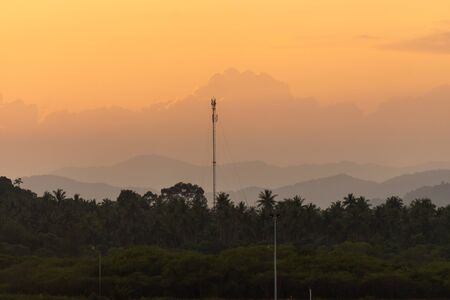 Photo pour Beautiful sunset scenic of moutain and coconut woods in suburb of Thailand with telecommunication pole in the middle of the photo. - image libre de droit