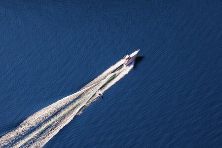Photo pour Aerial view of man wakeboarding on lake. Water skiing on lake behind a boat. - image libre de droit