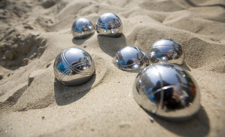 close-up of metal boccie balls in the sand