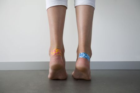 girl with colorful adhesive plasters on the blisters on her heels