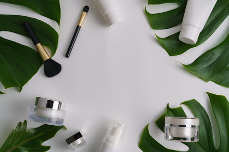Photo pour White cosmetic products and green leaves on white background. Natural beauty blank label for branding mock-up concept. - image libre de droit
