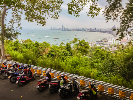 Beautiful view of Pattaya city from hilltop when looking through the gap between the trees.