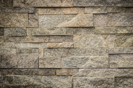 Beautiful pattern of old decorative stone wall background. Vintage stone wall Texture in weathered and have natural surfaces for design background. Featured pattern gray color of antique stone wall.