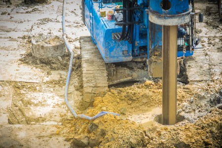 Photo for Hydraulic drilling machine is boring holes in the construction site for bored piles work. Bored piles are reinforced concrete elements cast into drilled holes, also known as replacement piles. - Royalty Free Image
