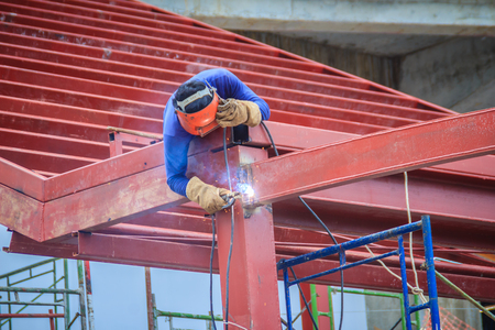Photo for Risky welder while climbing and welding on top of the steel roof structure work at the building construction site. Skilled worker is welding on the high steel structure at the construction project. - Royalty Free Image