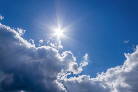 Foto de The sun and a white cloud in the blue sky on a beautiful summer day, as a background - Imagen libre de derechos