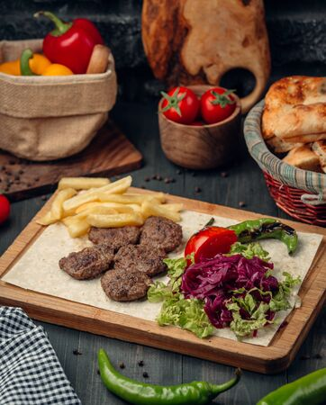 Photo pour Meat patties served with french fries and green salad - image libre de droit