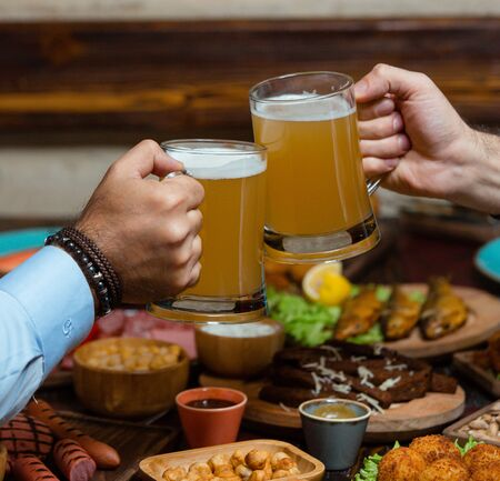 Photo pour Two friends clinking beer mugs in beew setup - image libre de droit