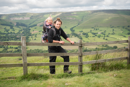 Happy young man enjoying  hiking with his little daughter in backpack child carrier