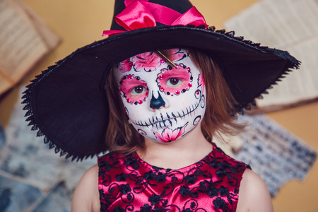 Girl in witch costume and makeup on her face