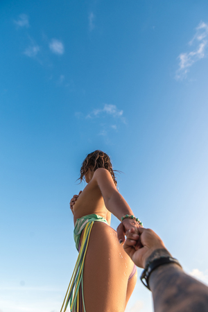 Photo pour Young woman holding boyfriend's hand on the beach. Follow me. - image libre de droit