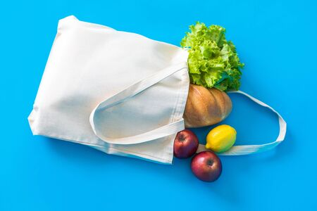 Foto per Cotton eco-bag with green fresh kale and fruits on the blue background. Eco friendly shopping. - Immagine Royalty Free
