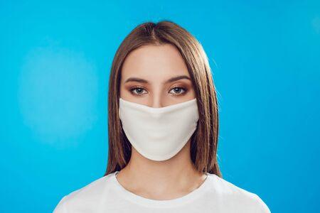 Photo pour Woman wearing face protective mask on face against Coronavirus on the blue background. - image libre de droit