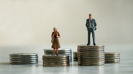 Concept of gender discrimination in pay. A miniature man and a miniature woman standing on top of a pile of coins.