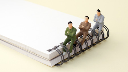 Three miniature men sitting and the wire bound notebook pad.