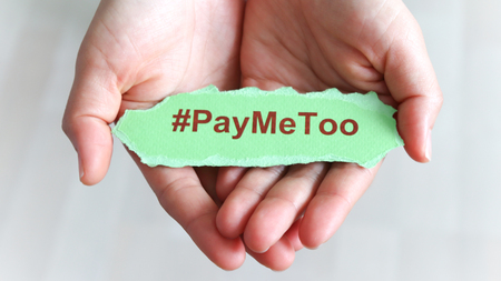 #PayMeToo as a new social movement. A piece of paper with #PayMeToo written on the palm of a woman's hand.