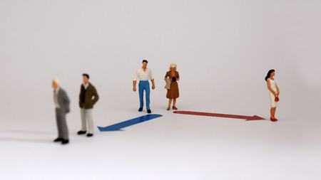 Miniature men and women walking in different directions. The concept of the division of roles between men and women in society.