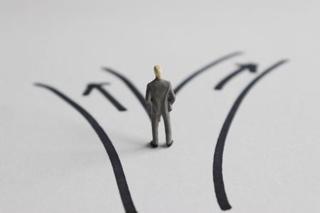 Photo pour A miniature man standing in front of two paths. - image libre de droit