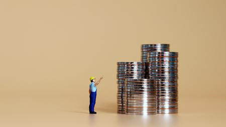 Photo pour A pile of coins and a miniature man pointing to them. - image libre de droit