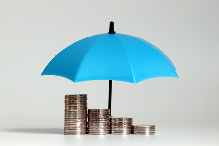 Photo pour A pile of coins and open blue umbrellas. - image libre de droit