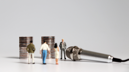Two piles of coins and miniature people with a microphone.