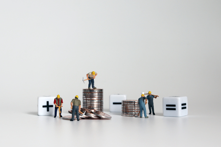 Miniature worker people with a cube with an arithmetic symbol and piles of coins.