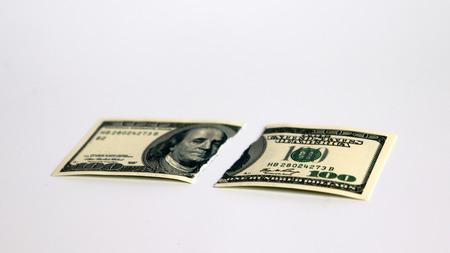 A hundred dollar bill torn in half.