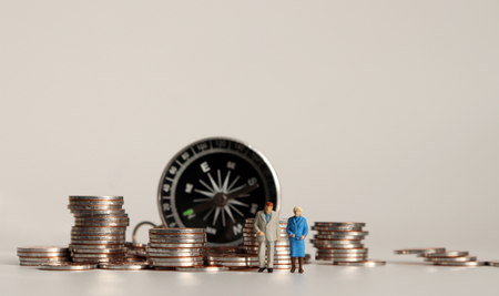 Foto de Compass and pile of coins. A miniature old couple. - Imagen libre de derechos