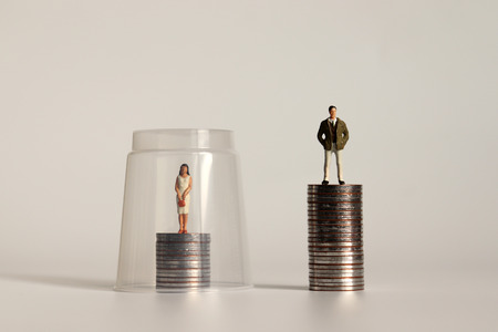 Photo for A glass ceiling concept. A miniature man and a miniature woman standing on a pile of coins of different heights. - Royalty Free Image