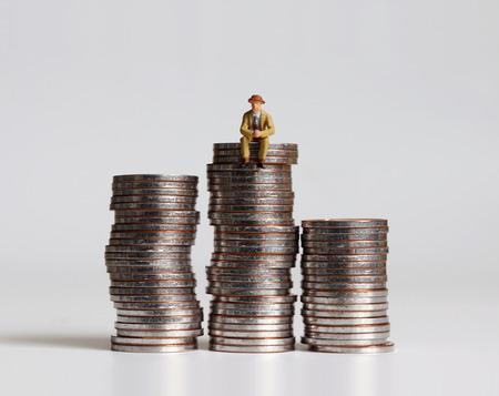 Photo pour A miniature man sitting on a pile of coins. - image libre de droit