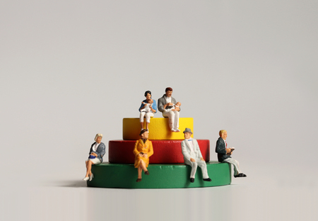 Photo pour Miniature people sitting on wooden blocks. - image libre de droit