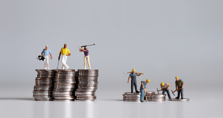 Photo pour Miniature people standing on a pile of coins. A concept of income disparity. - image libre de droit