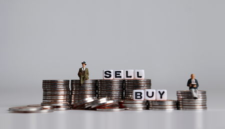 Photo pour Two miniature people and white cubes with the words BUY SELL on pile of coins. - image libre de droit