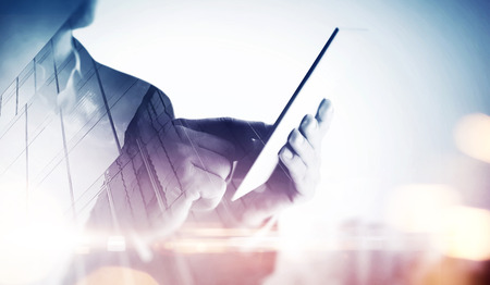 Foto de Double exposure of a city and businessman with digital tablet - Imagen libre de derechos